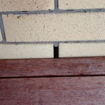 Timber decking, partly encumbering weep hole